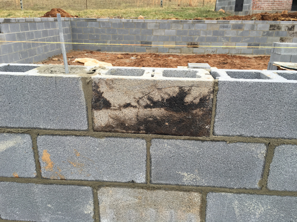 Blackened cinder blocks from our first oven make it into the foundation